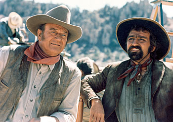 "John Wayne and Pedro Armendariz Jr. take a break from filming  ""The Undefeated"" ('69 20th Century Fox)."