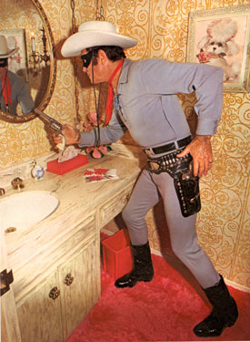 "A latter day Clayton Moore (""Lone Ranger"") practices his draw in front of a mirror in his suburban Hollywood home."