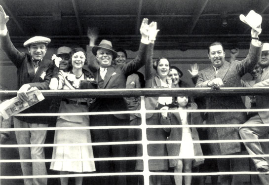 "Western star Hoot Gibson prepares to sail to Hawaii with wife Sally Eilers for her role in the Charlie Chan mystery ""The Black Camel"" ('31). Also in the cast are Bela Lugosi (left) and 'Chan' Warner Oland (waving his hat). Director Hamilton MacFadden leans on the railing beside Oland."