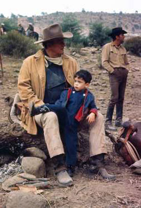 "John Wayne with three-year old son Ethan on location for ""The Sons of Katie Elder"" ('65). Costar Dean Martin looks off in the distance."