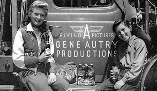 Gail Davis as Annie Oakley and Jimmy Hawkins as her kid brother Tagg pause beside a Gene Autry Flying A equipment truck in 1953 to enjoy some Canada Dry. (Photo courtesy Jimmy Hawkins.)