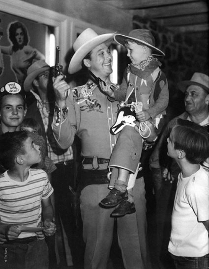 "Monte Hale entertains a group of young fans at a theatre in 1946. (Note the poster of Jane Russell in ""The Outlaw"" behind Monte.) (Photo courtesy Mrs. Joanne Hale and The Autry National Center.)"