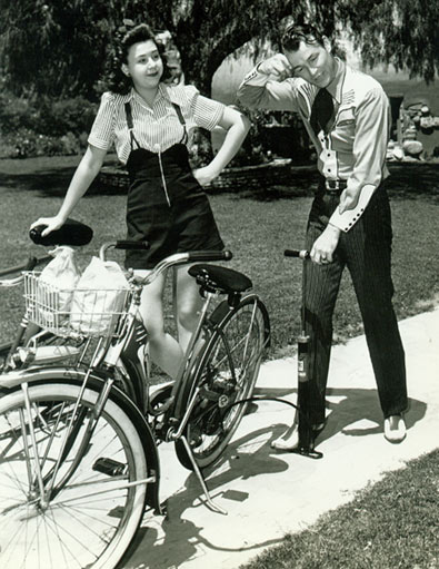 Roy Rogers tries to help Jane Withers with a flat bicycle tire.