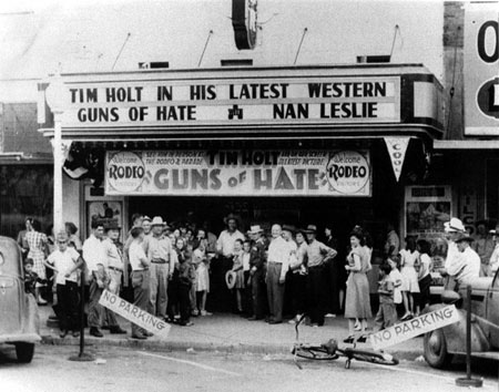 "What a day this must have been in Mangum, OK, in August 1948! RKO's Tim Holt was in Mangum for a rodeo and parade and stopped off at not just one, but two, theatres both showing ""Guns of Hate"" ('48). Top photo shows Tim at the Temple Theatre with the bottom photo taken at the Greer Theatre the same day. (Photos courtesy Billy Holcomb.)"