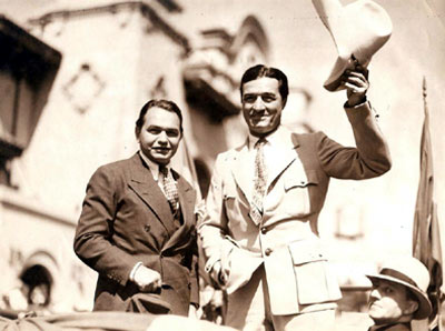 Screen gangster Edward G. Robinson and screen cowboy Tom Mix greet the public. Circa late '30s.