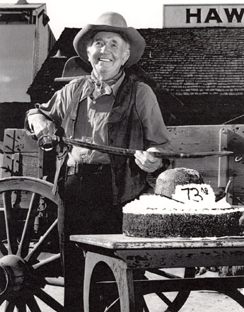 "Walter Brennan jokingly celebrates his 73rd birthday on the set of his series ""The Guns of Will Sonnett"". (Photo courtesy Neil Summers.)"