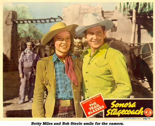 "Betty Miles and Bob Steele smile for the camera on the scene card from ""Sonora Stagecoach""."