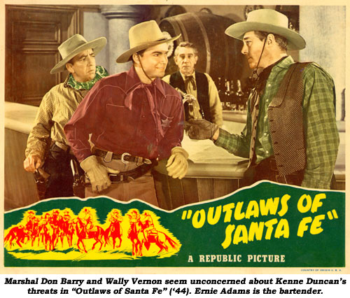 "Marshal Don Barry and Wally Vernon seem unconcerned about Kenne Duncan's threats in ""Outlaws of Santa Fe"" ('44). Ernie Adams is the bartender."