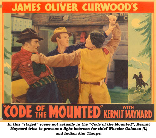 "In this ""staged"" scene not actually in the ""Code of the Mounted"", Kermit Maynard tries to prevent a fight between fur thief Wheeler Oakman (L) and Indian Jim Thorpe."